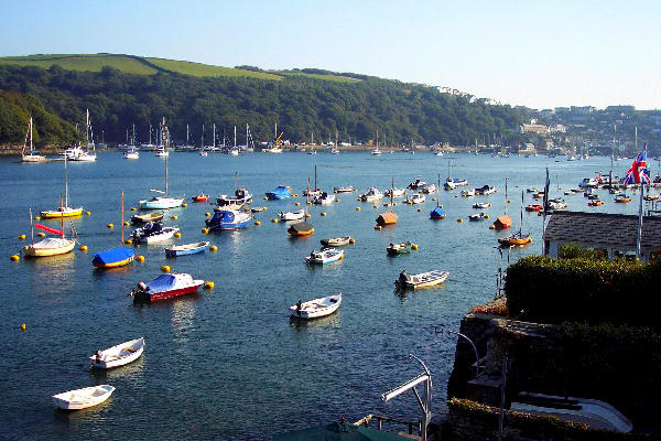 Photograph of myriad picturesque craft moored in Fowey harbour together with the collage of trees and buildings clinging to the hillside at Polruan, beyond